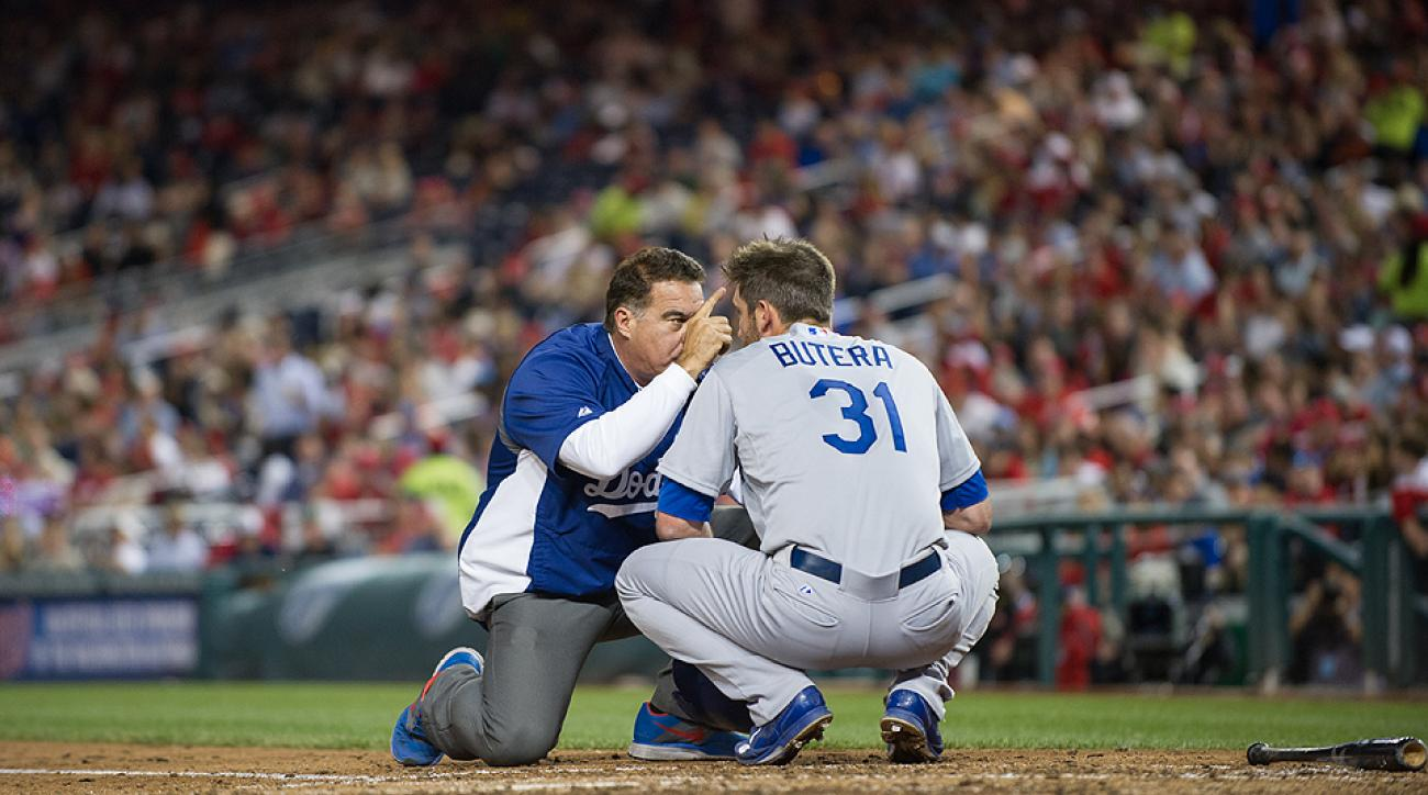 Drew Butera of the Los Angeles Dodgers is examined for concussion-related symptoms by a trainer during a game against the Washington Nationals.
