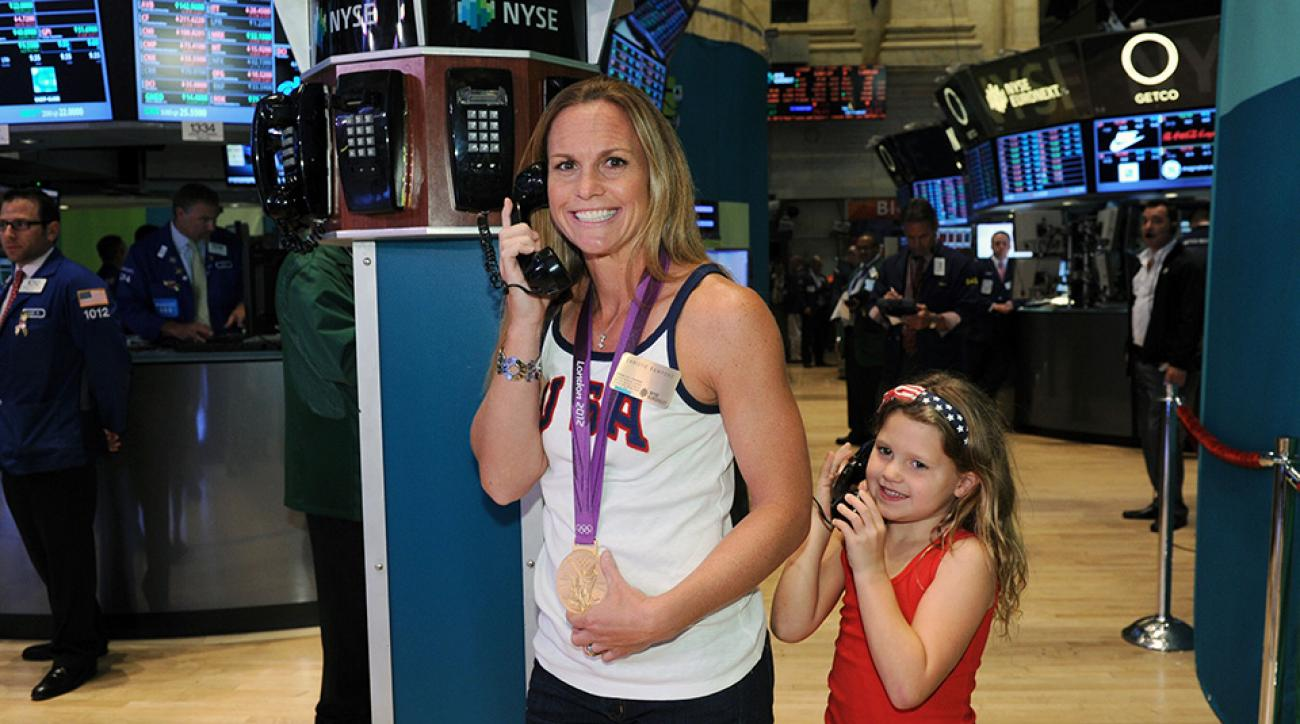 Christie Rampone poses with her Olympic gold medal and her daughter as she prepares to ring the opening bell at the New York Stock Exchange.