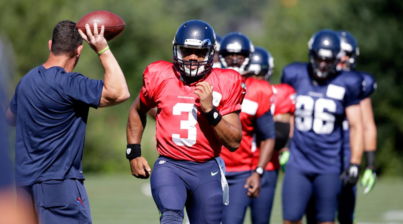 Seattle Seahawks quarterback Russell Wilson (3) and backup quarterbacks Tarvaris Jackson (7) and B.J. Daniels (5) take part in an agility drill during NFL Football training camp, Thursday, July 31, 2014, in Renton, Wash.