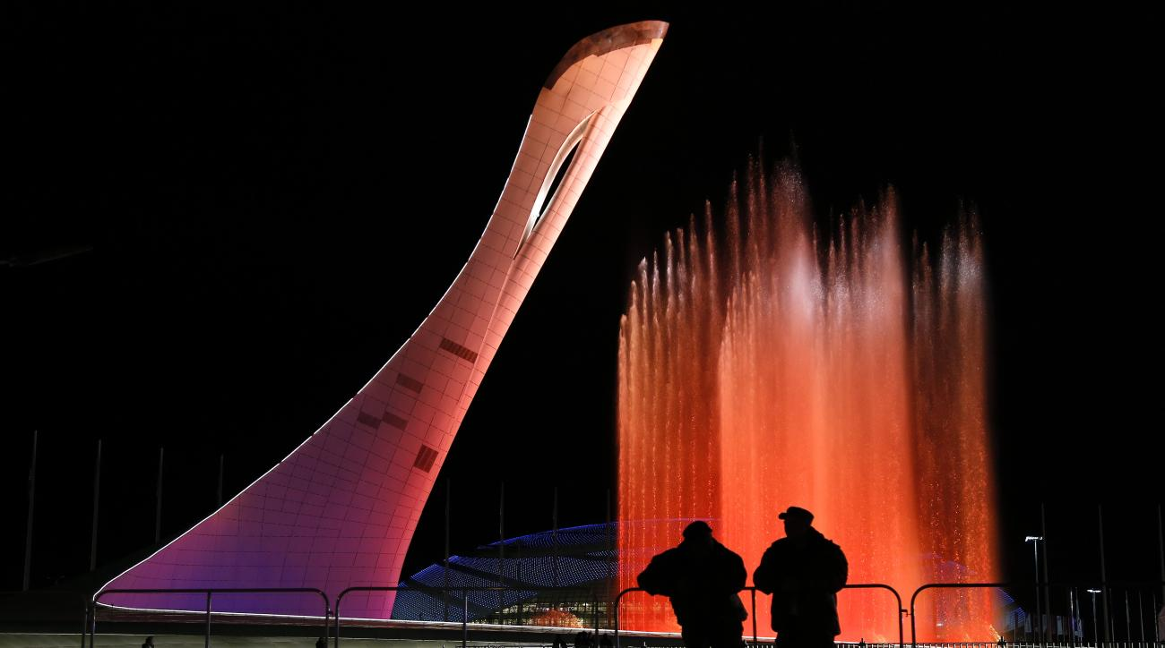 """Security personnel watch a practice run of a fountain show to music from """"Swan Lake"""" on the perimeter of the Olympic cauldron in preparation for the 2014 Winter Olympics, Thursday, Feb. 6, 2014, in Sochi, Russia. The cauldron will be lit with the Olympic torch during Friday's opening ceremonies. (AP Photo/Julie Jacobson)"""