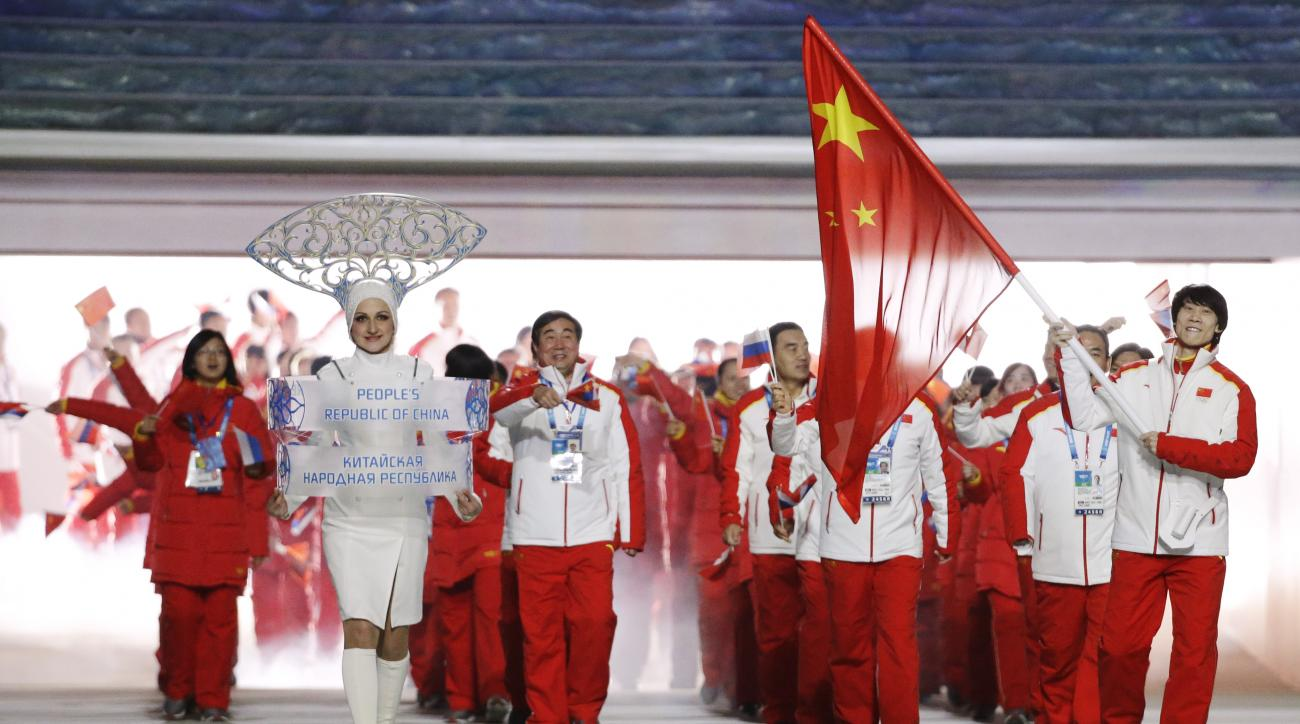 Tong Jian of China carries the national flag as he leads the team during the opening ceremony of the 2014 Winter Olympics in Sochi, Russia, Friday, Feb. 7, 2014. (AP Photo/Mark Humphrey)