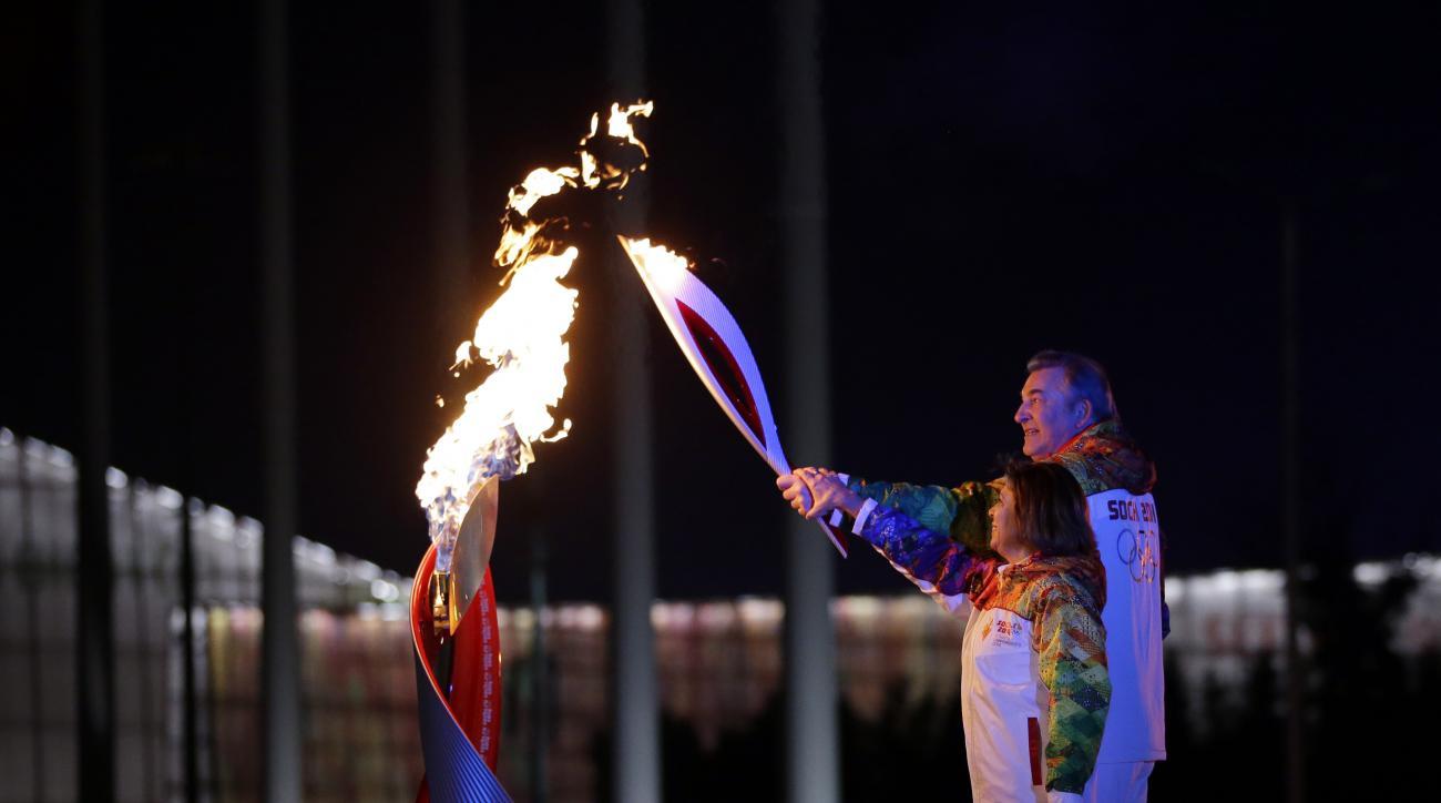 Irina Rodnina and Vladislav Tretiak light the Olympic cauldron during the opening ceremony of the 2014 Winter Olympics in Sochi, Russia, Friday, Feb. 7, 2014. (AP Photo/Matt Slocum, Pool)
