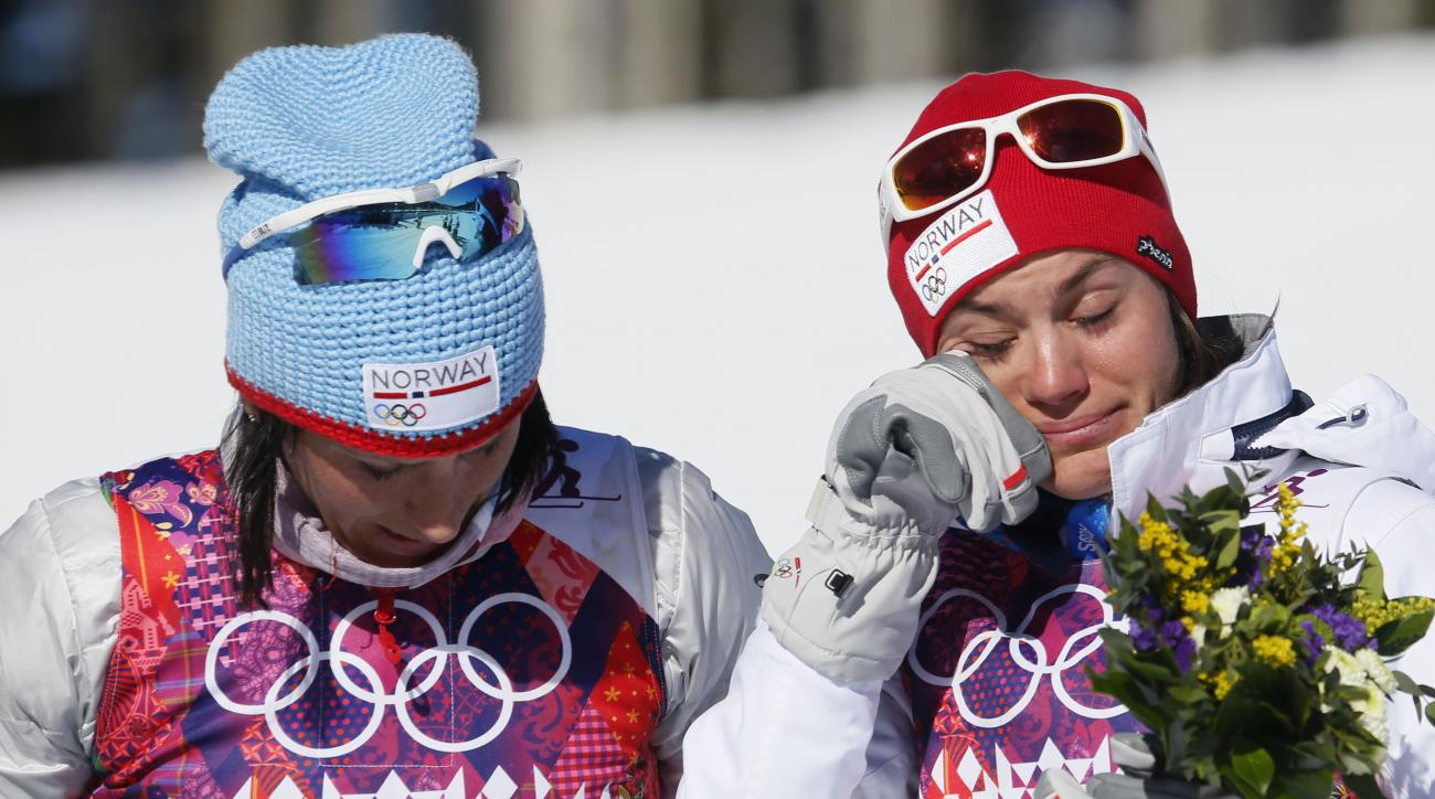Norway's bronze medal winner Heidi Weng, right, cries on the podium beside gold medal winner Marit Bjoergen  during the flower cwomen's cross-country 15k skiathlon at the 2014 Winter Olympics, Saturday, Feb. 8, 2014, in Krasnaya Polyana, Russia. (AP Photo/Dmitry Lovetsky)