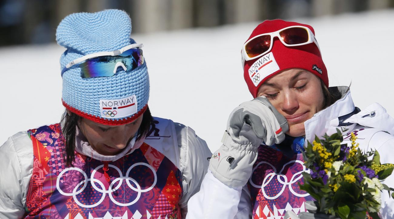 Norway's bronze medal winner Heidi Weng, right, cries on the podium beside gold medal winner Marit Bjoergen  during the flower cwomen's cross-country 15k skiathlon at the 2014 Winter Olympics, Saturday, Feb. 8, 2014, in Krasnaya Polyana, Russia. (AP Photo/Dmitry Lovetsky)
