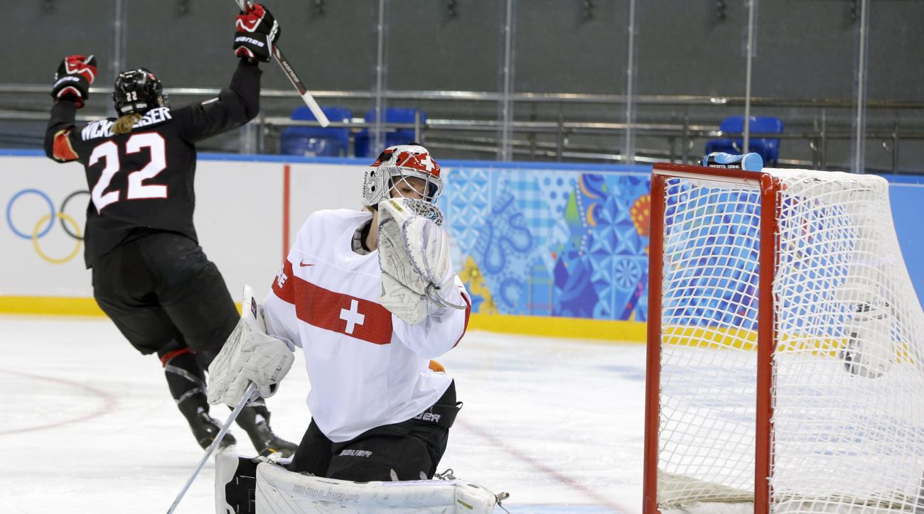 Goalkeeper Florence Schelling of Switzerland looks back at the puck in the net as Hayley Wickenheiser of Canada celebrates her goal during the second period of the women's ice hockey game at the Shayba Arena during the 2014 Winter Olympics, Saturday, Feb. 8, 2014, in Sochi, Russia. (AP Photo/Matt Slocum)