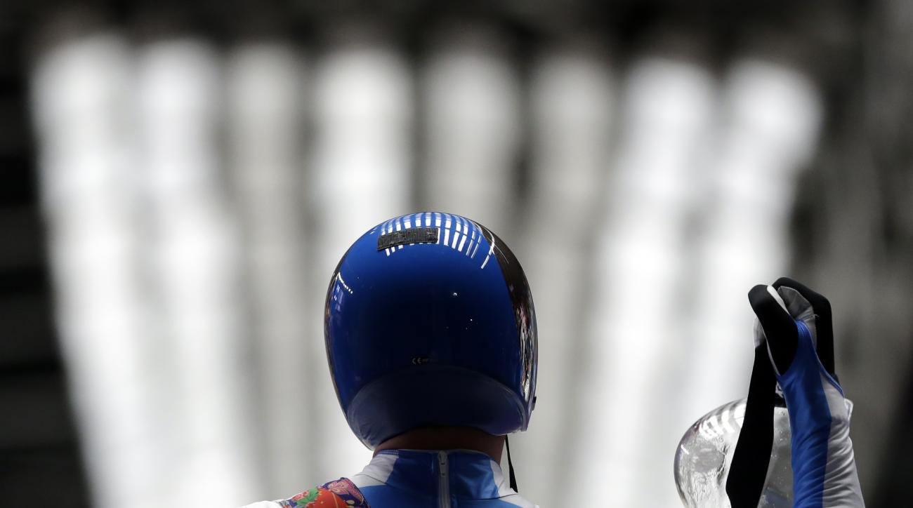 Armin Zoeggeler of Italy waves to supporters after finishing his second run during the men's singles luge competition at the 2014 Winter Olympics, Saturday, Feb. 8, 2014, in Krasnaya Polyana, Russia. (AP Photo/Dita Alangkara)