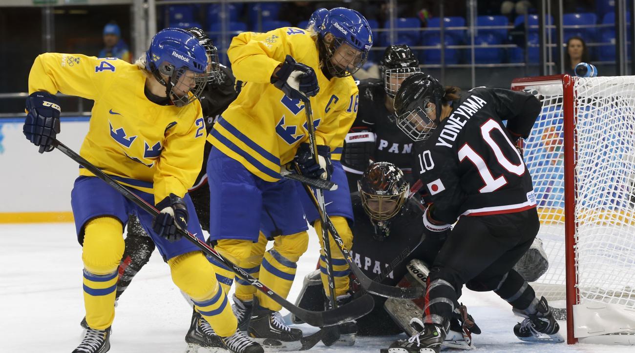 Erika Grahm and Jenni Asserholt of Sweden battle Goalkeeper Nana Fujimoto and Haruna Yoneyama of Japan, (L-R) in front of the net during the 2014 Winter Olympics women's ice hockey game at Shayba Arena, Sunday, Feb. 9, 2014, in Sochi, Russia. (AP Photo/Petr David Josek)