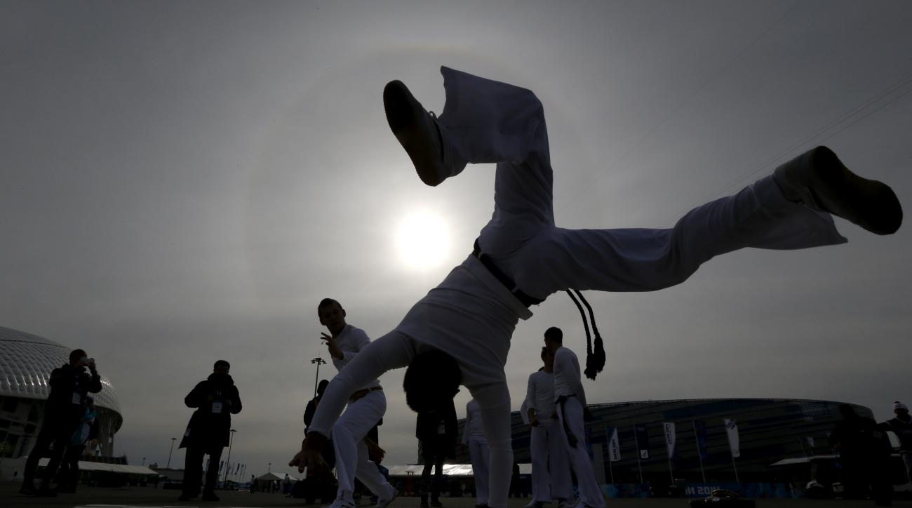Street performers dance capoeira as a crowd watches in Olympic Park during the 2014 Winter Olympics, Sunday, Feb. 9, 2014, in Sochi, Russia. (AP Photo/Julio Cortez)