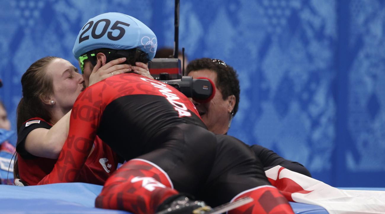 Charles Hamelin of Canada, right, embraces Marianne St. Gelais after he won the men's 1500m short track speedskating final at the Iceberg Skating Palace during the 2014 Winter Olympics, Monday, Feb. 10, 2014, in Sochi, Russia. (AP Photo/Darron Cummings)