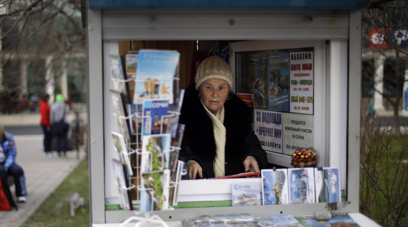 """In this photo taken Monday, Feb. 10, 2014, 74-year-old Sochi native Dina Kobolenko waits for tourists in her kiosk selling maps, books and postcards outside the central train station in Sochi, Russia. Vladimir Putin isn't the only one who has a lot riding on the success of the Sochi Olympics. Local businesses and residents have a lot to gain if these Olympics fulfill Putin's pledge to turn Sochi and its environs from a summer playground for well-off Russians into a year-round international resort for everyone. But that's a big """"if."""" But for all the money spent on Olympic infrastructure, Kobolenko said, """"This was a village, is a village and will remain a village,"""" not Russia's answer to Las Vegas or Dubai. (AP Photo/David Goldman)"""