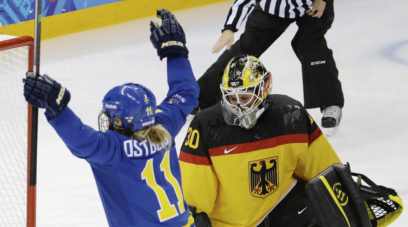 Goalkeeper Jennifer Harss of Germany looks down as Cecilia Ostberg of Sweden celebrates her goal during the third period of the 2014 Winter Olympics women's ice hockey game at Shayba Arena, Tuesday, Feb. 11, 2014, in Sochi, Russia. (AP Photo/Mark Humphrey)