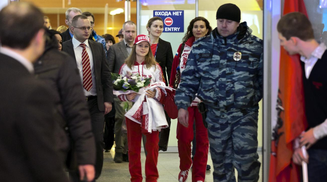 """Russian Julia Lipnitskaia, center, walks through a corridor surrounded by police officers in the Sheremetyevo airport, outside Moscow, Russia, Tuesday, Feb. 11, 2014.Russian figure-skating 15-year-old phenomenon Lipnitskaia has returned to Moscow to train for what she hopes will be another gold medal. She already has one in the team skating and says it is """"very heavy but beautiful."""" Next on her agenda is the women's competition, which begins Feb. 19 in Sochi. Until then, Lipnitskaia plans to train in Moscow. (AP Photo/Alexander Zemlianichenko)"""