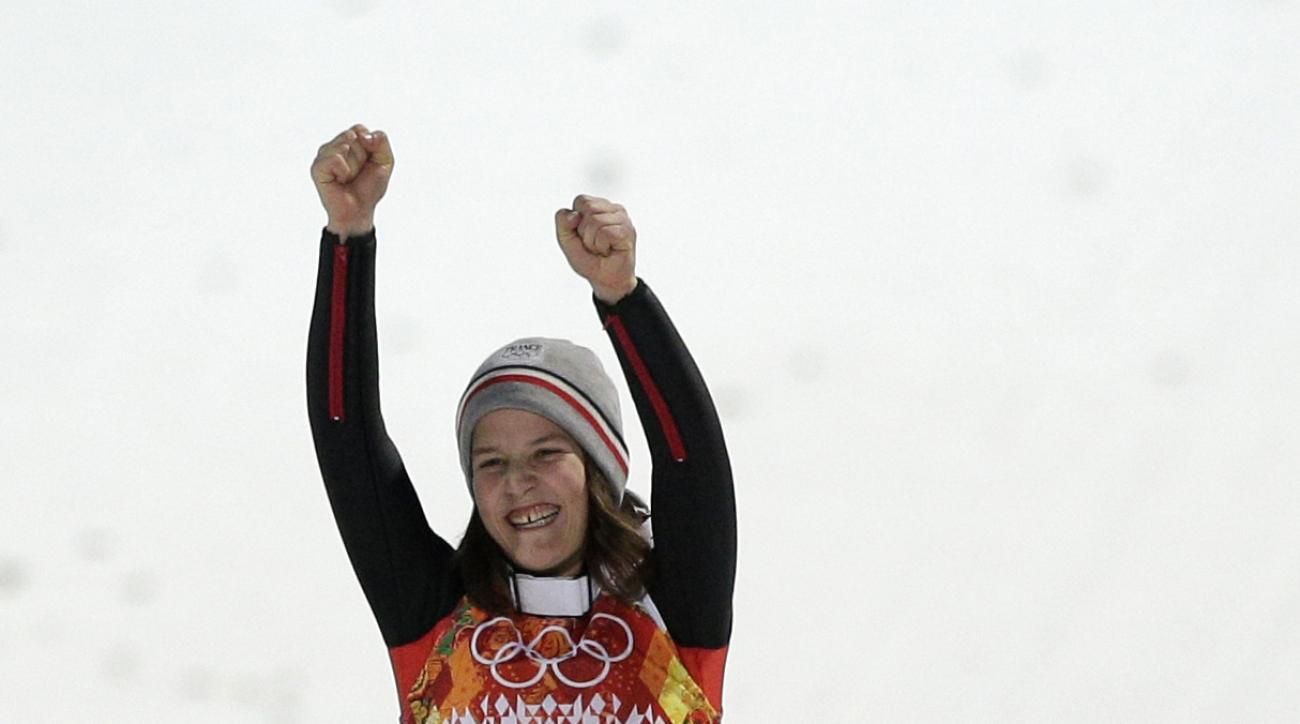 France's Coline Mattel celebrates winning the bronze during flower ceremony for the women's normal hill ski jumping final at the 2014 Winter Olympics, Tuesday, Feb. 11, 2014, in Krasnaya Polyana, Russia. (AP Photo/Matthias Schrader)