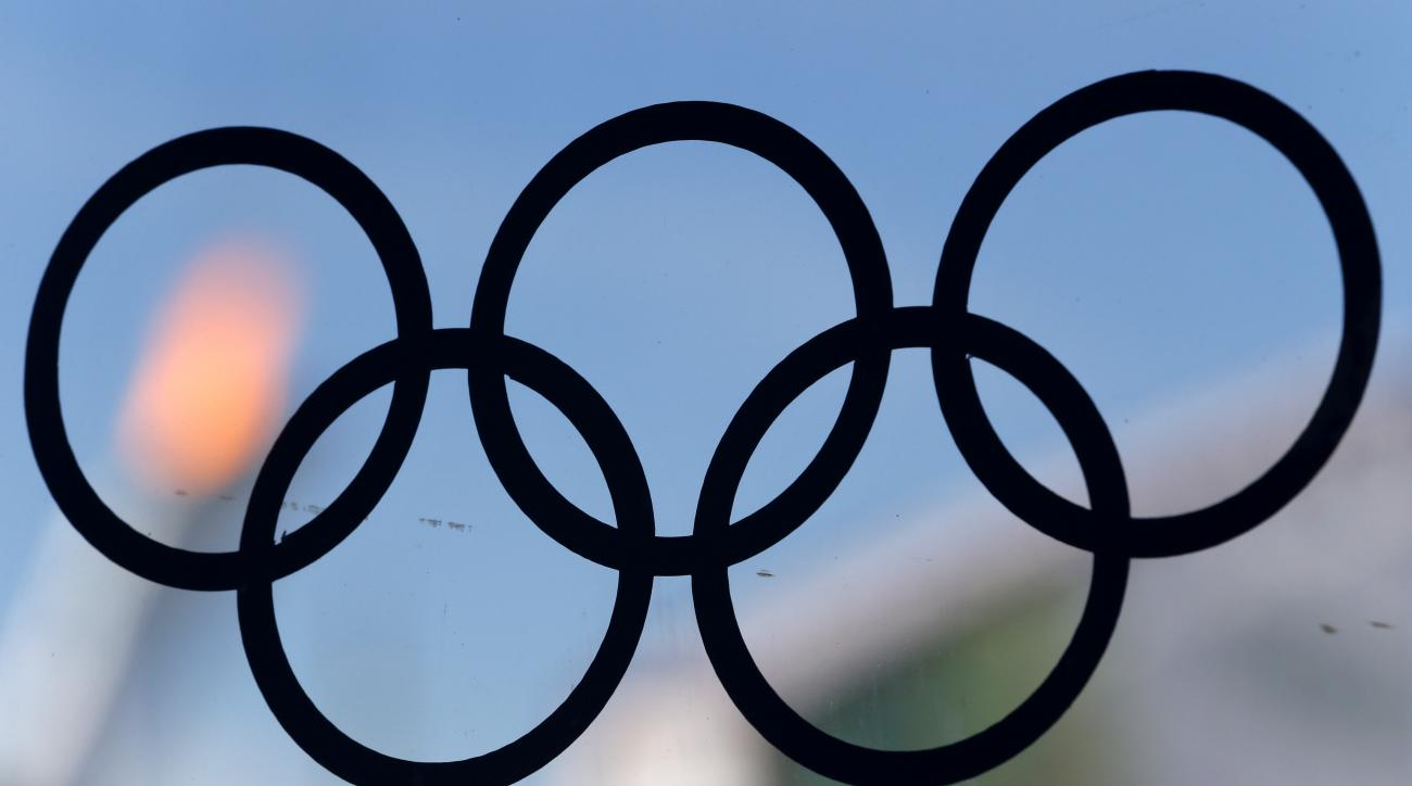 The flame of the Olympic cauldron is viewed through a glass panel with a sticker of the Olympic rings at a food court in Olympic Park in Sochi, Russia, during the 2014 Winter Olympics, Wednesday, Feb. 12, 2014. (AP Photo/Julio Cortez)