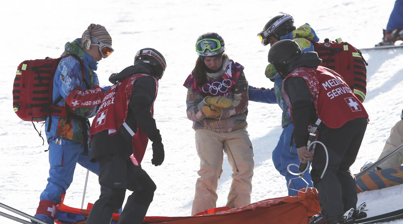 United States' Arielle Gold is assisted after injuring her hand in a crash during the women's snowboard halfpipe qualifying at the Rosa Khutor Extreme Park, at the 2014 Winter Olympics, Wednesday, Feb. 12, 2014, in Krasnaya Polyana, Russia. (AP Photo/Sergei Grits)