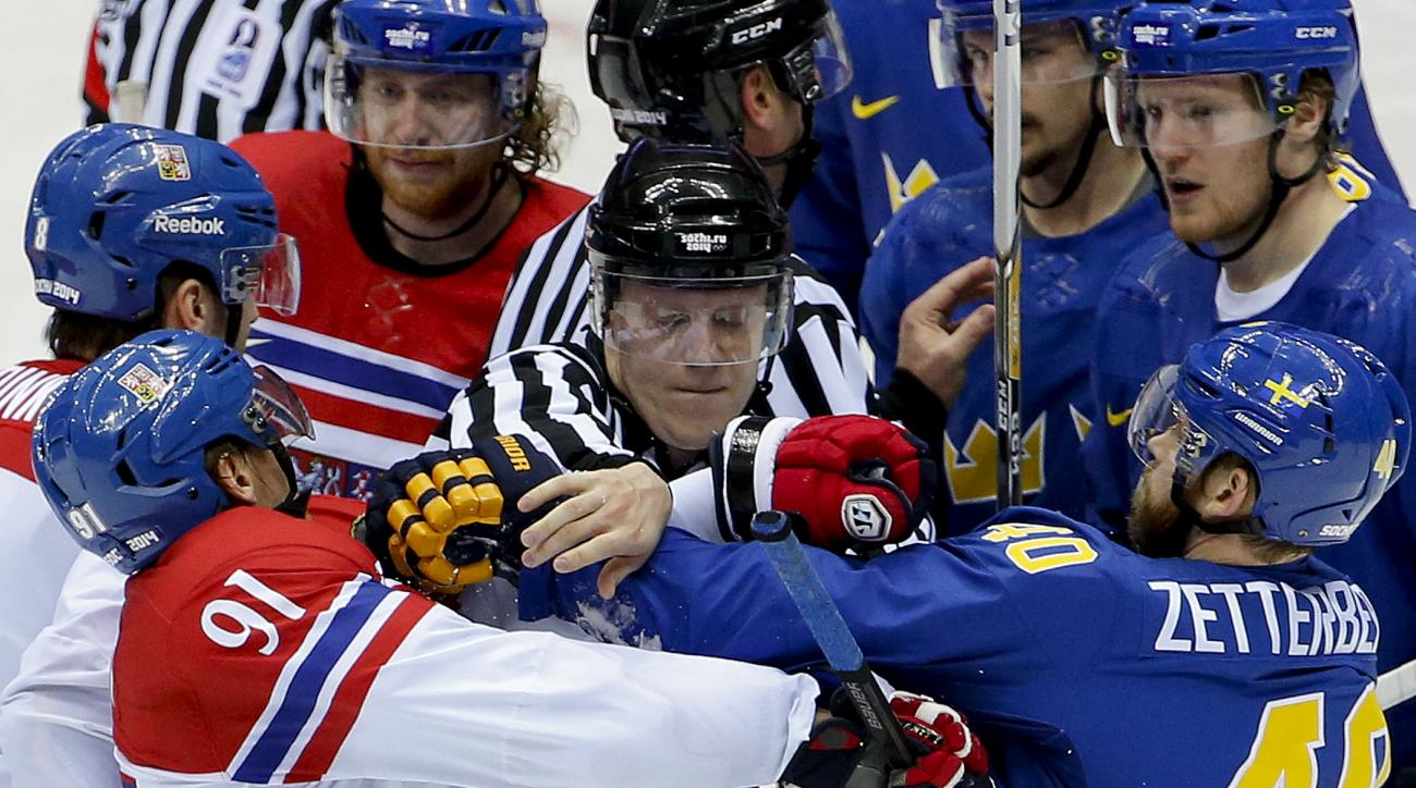 A linesman breaks up a scuffle between Czech Republic forward Martin Erat (91) and Sweden forward Henrik Zetterberg in the third period of a men's ice hockey game at the 2014 Winter Olympics, Wednesday, Feb. 12, 2014, in Sochi, Russia. (AP Photo/Julio Cortez)