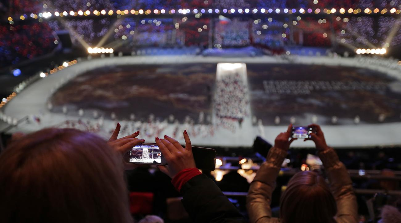 FILE - In this  Friday, Feb. 7, 2014, file photo, a spectator takes a video of the opening ceremony on her mobile phone at the 2014 Winter Olympics in Sochi, Russia.  (AP Photo/Charlie Riedel, File)