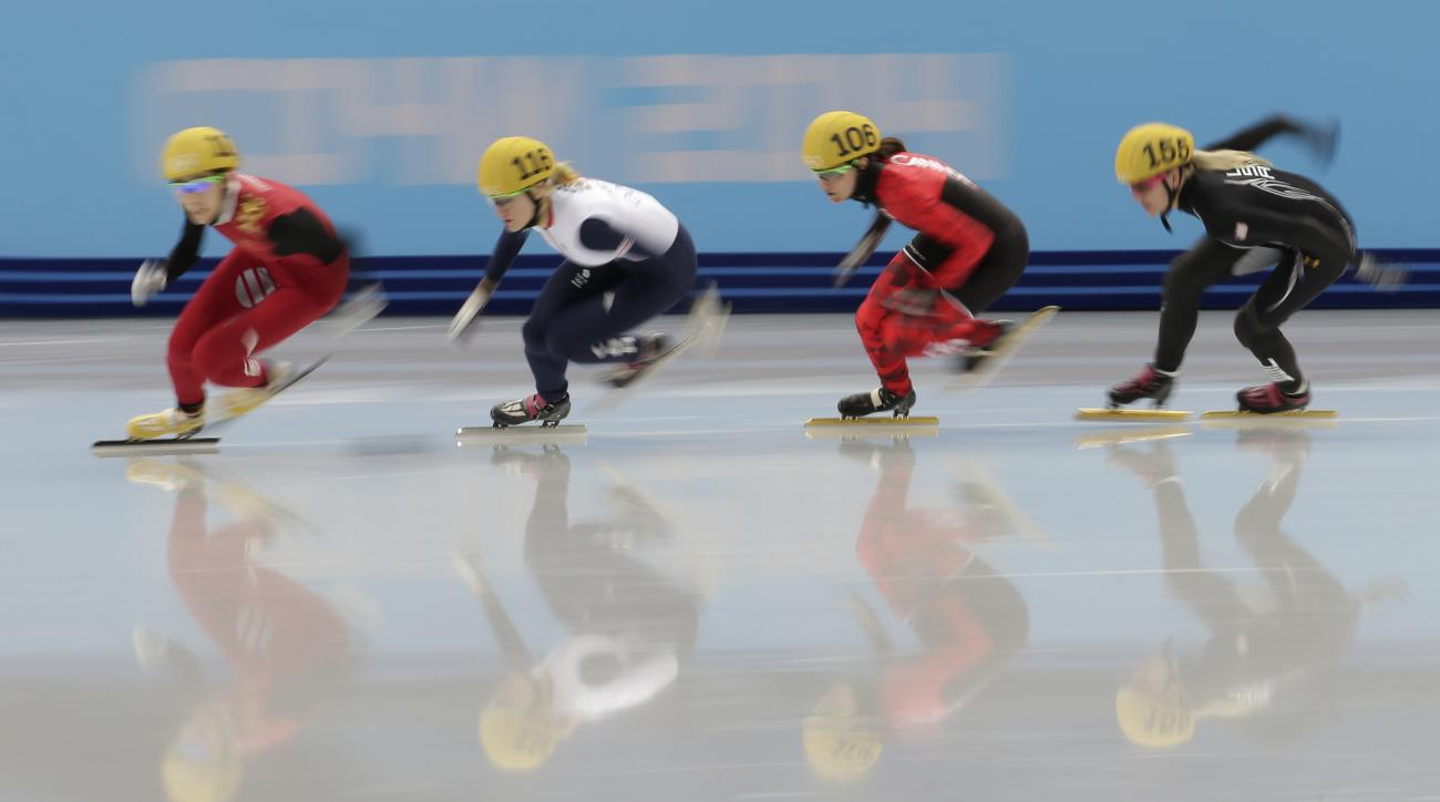 Fan Kexin of China, Elise Christie of Britain, Jessica Hewitt of Canada and Emily Scott of the United States compete in a women's 500m short track speedskating quarterfinal at the Iceberg Skating Palace during the 2014 Winter Olympics, Thursday, Feb. 13, 2014, in Sochi, Russia. (AP Photo/Bernat Armangue)