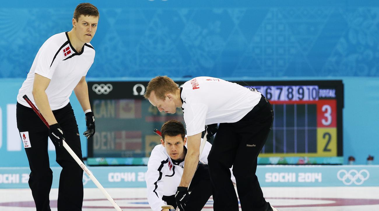 Denmark's skip Rasmus Stjerne Hansen, center, delivers the rock as Troels Harry, left, and Mikkel Poulsen, right, sweep the ice during the men's curling competition against Canada at the 2014 Winter Olympics, Thursday, Feb. 13, 2014, in Sochi, Russia. (AP Photo/Wong Maye-E)