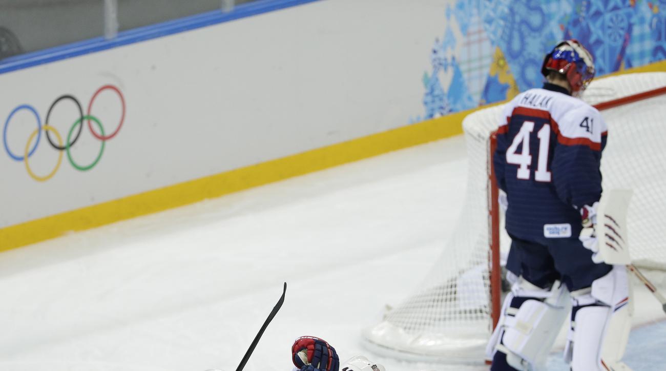 Team USA celebrates Paul Stastny's goal as Slovakia goaltender Jaroslav Halak skates in front of the net during the 2014 Winter Olympics men's ice hockey game at Shayba Arena, Thursday, Feb. 13, 2014, in Sochi, Russia. (AP Photo/Matt Slocum)