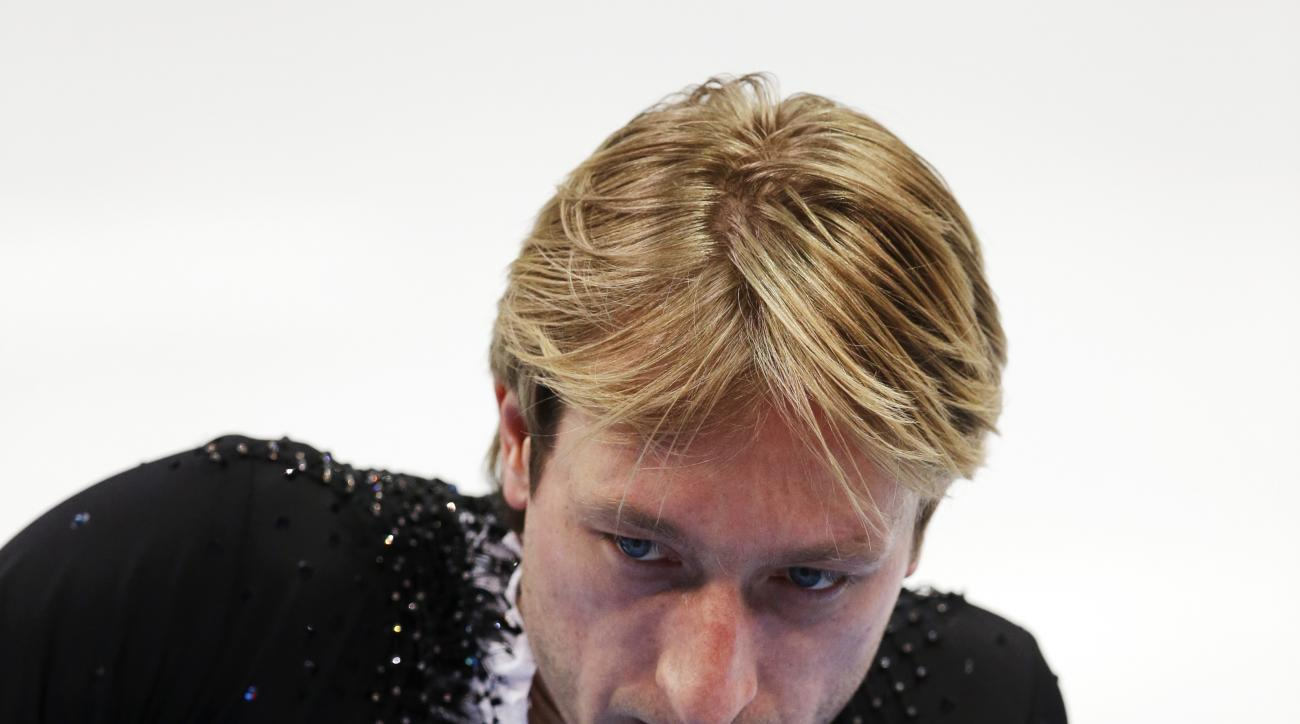 Evgeni Plushenko of Russia leaves the ice after pulling out of the men's short program figure skating competition due to illness at the Iceberg Skating Palace during the 2014 Winter Olympics, Thursday, Feb. 13, 2014, in Sochi, Russia. (AP Photo/Darron Cummings)