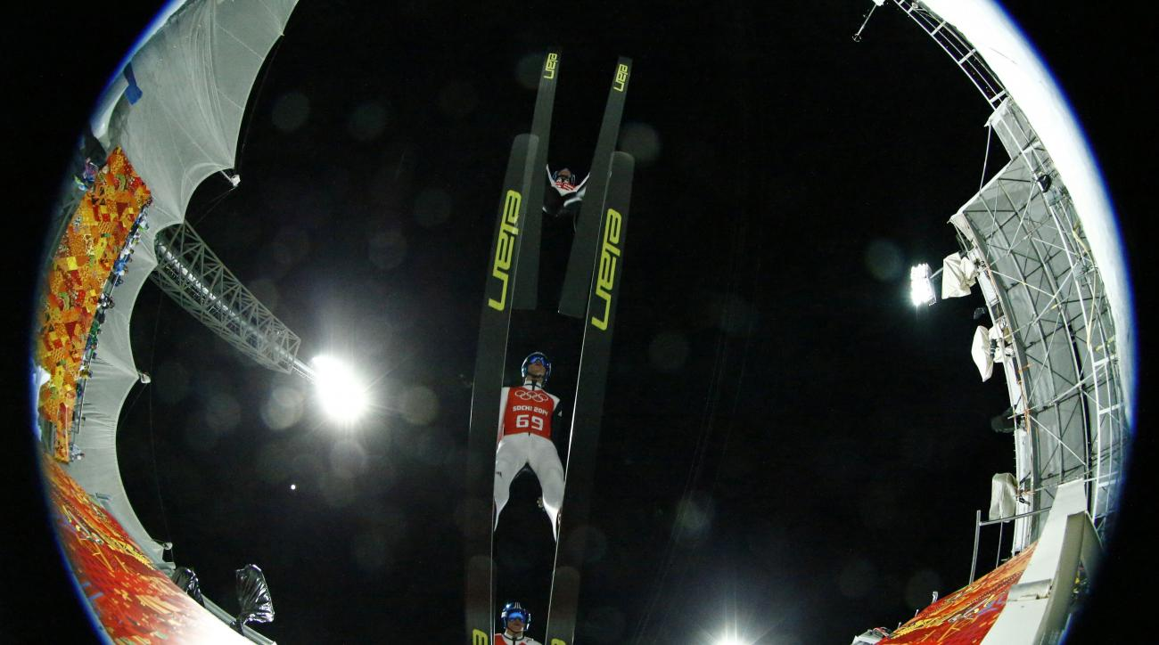 In this multiple exposure photo taken with a fisheye lens Slovenia's Peter Prevc makes his jump during the men's large hill ski jumping training session at the 2014 Winter Olympics, Thursday, Feb. 13, 2014, in Krasnaya Polyana, Russia. (AP Photo/Dmitry Lovetsky)