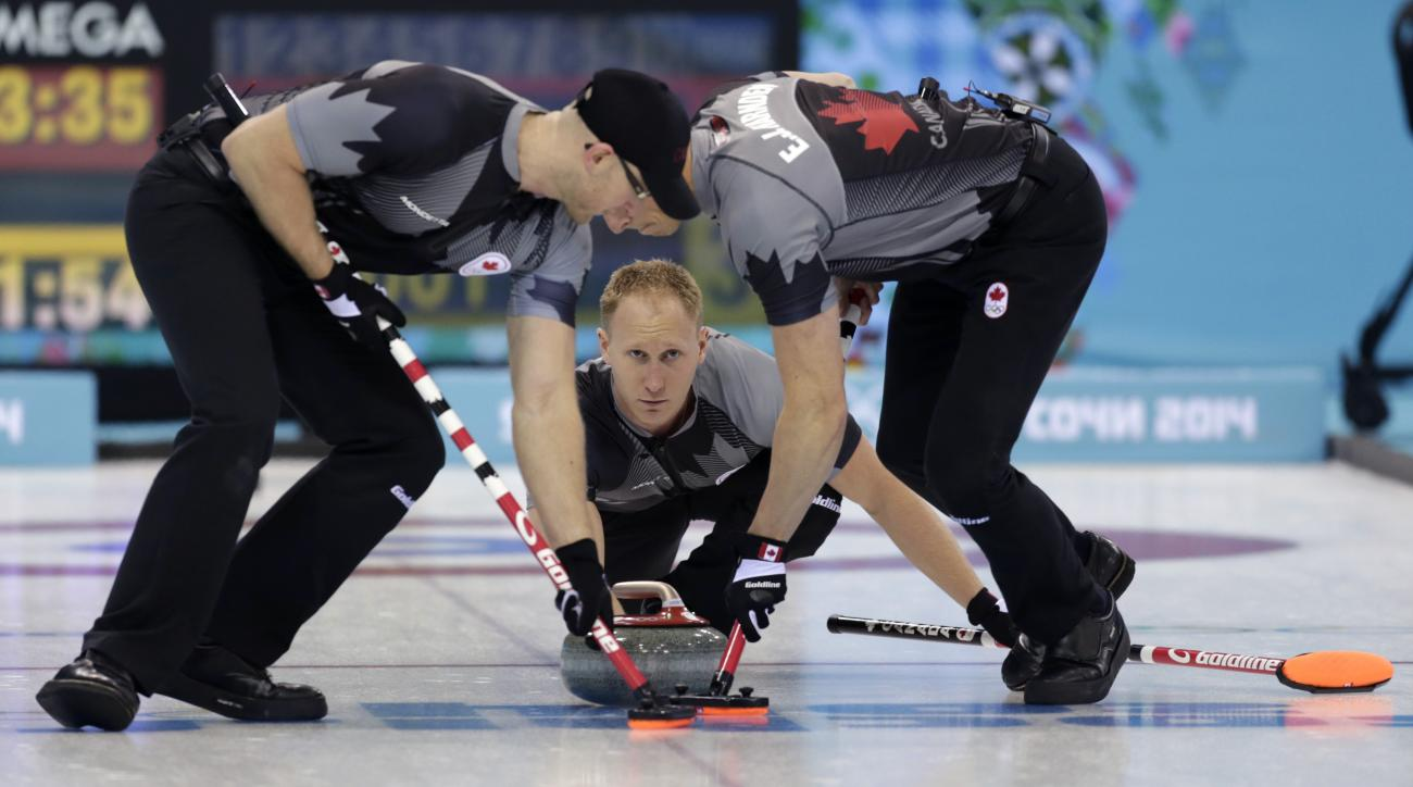 Canada's skip Brad Jacobs, center, delivers the rock to his sweepers Ryan Harnden, left, and E.J. Harnden during men's curling competition against Norway at the 2014 Winter Olympics, Friday, Feb. 14, 2014, in Sochi, Russia. (AP Photo/Robert F. Bukaty)