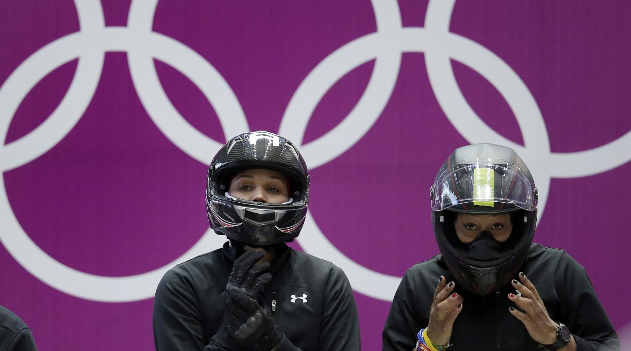 Jazmine Fenlator, right, and Lolo Jones of the United States prepare for a heat race of the women's bobsleigh competition at the 2014 Winter Olympics,  Friday, Feb. 14, 2014, in Krasnaya Polyana, Russia. (AP Photo/Michael Sohn)