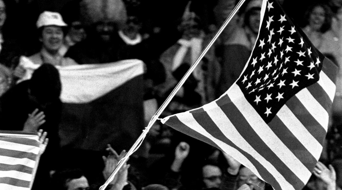 "FILE - In this Feb. 16, 1984 file photo, figure skater Scott Hamilton of the United States carries an American flag past a cheering crowd after he was awarded a gold medal in figure skating at the 1984 Winter Games at Zetra's ice rink in Sarajevo. In the thirty years since his victory, Hamilton has pretty much reinvented professional figure skating by creating ""Stars On Ice"" and has been the voice of the sport for decades. (AP Photo/File)"