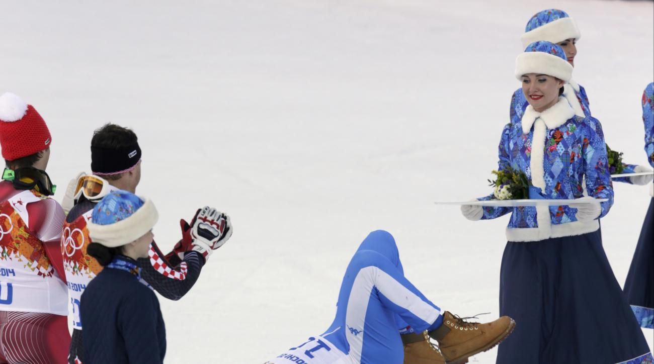 Men's supercombined bronze medal winner Christof Innerhofer lies on the podium after doing a headstand during a flower ceremony at the Alpine ski venue at the Sochi 2014 Winter Olympics, Friday, Feb. 14, 2014, in Krasnaya Polyana, Russia. (AP Photo/Charles Krupa)