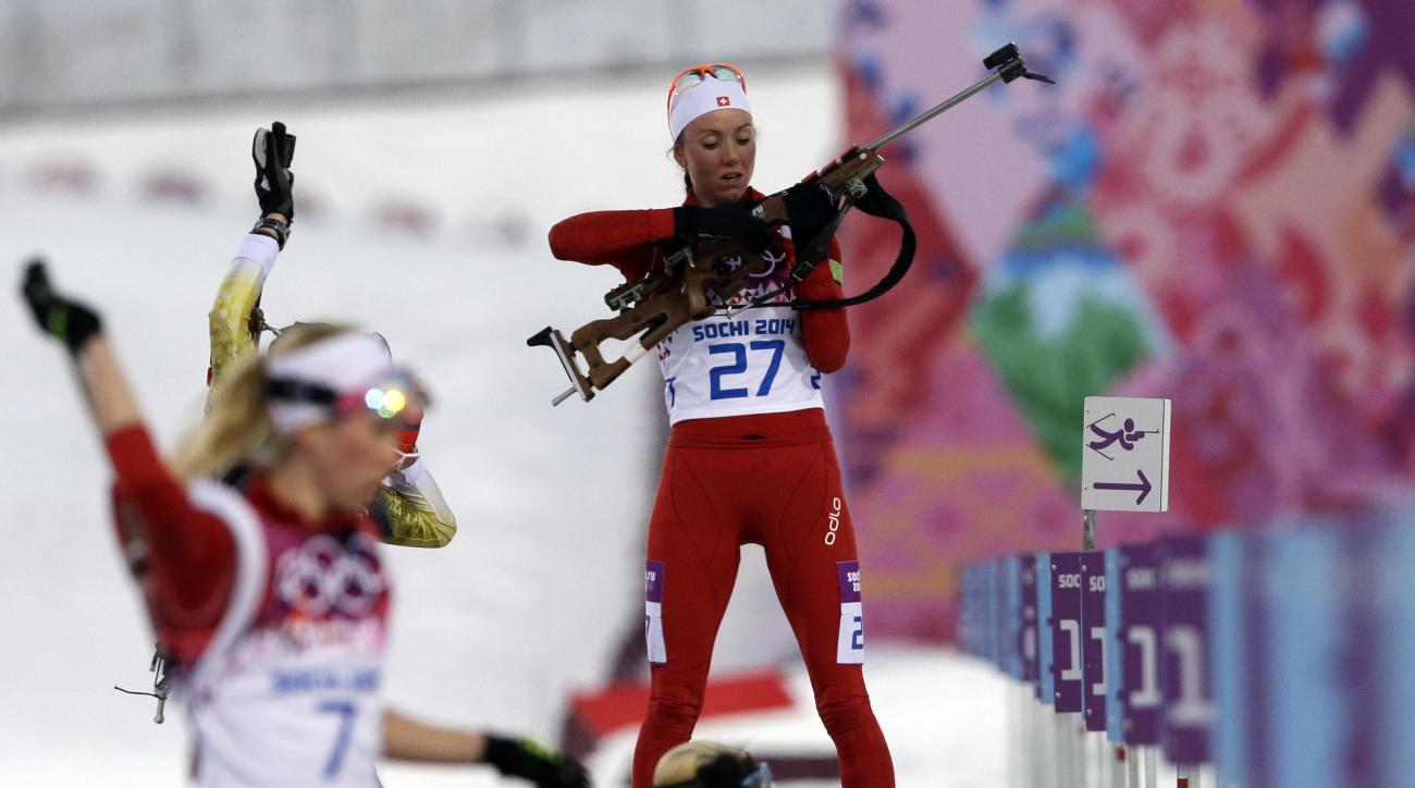 Switzerland's Selina Gasparin prepares to shoot as her sister Elisa is seen at left, during the women's biathlon 15k individual race, at the 2014 Winter Olympics, Friday, Feb. 14, 2014, in Krasnaya Polyana, Russia. (AP Photo/Lee Jin-man)