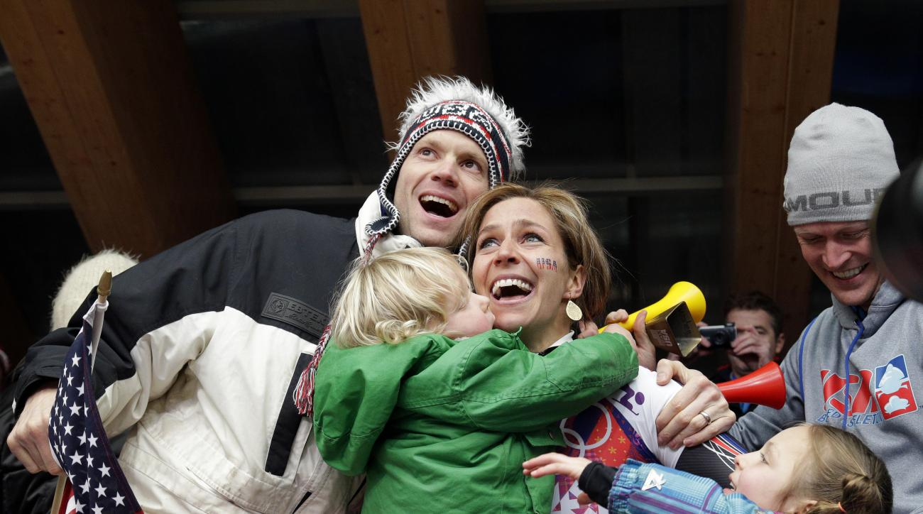 Noelle Pikus-Pace of the United States hugs her husband, Janson Pace, and children, Traycen, left, and Lacee, right, after she won the silver medal during the women's skeleton competition at the 2014 Winter Olympics, Friday, Feb. 14, 2014, in Krasnaya Polyana, Russia. (AP Photo/Michael Sohn)