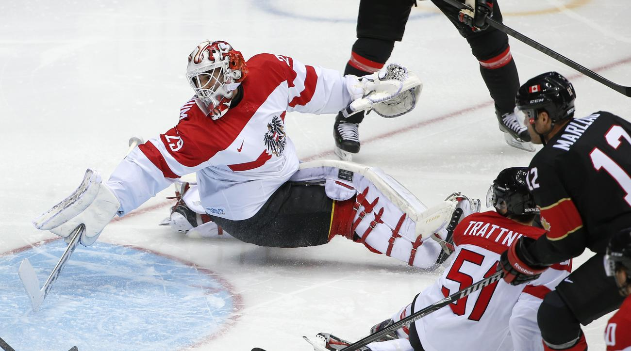 Austria goaltender Bernhard Starkbaum reaches back as the puck shot by Canada forward Jeff Carter, flies into the net for a goal in the second period of a men's ice hockey game at the 2014 Winter Olympics, Friday, Feb. 14, 2014, in Sochi, Russia. (AP Photo/Julio Cortez)