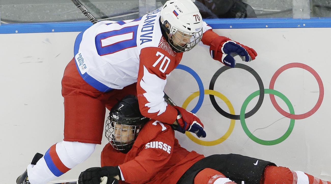 Anna Shibanova of Russia and Lara Stalder of Switzerland collide during the 2014 Winter Olympics women's ice hockey quarterfinal game at Shayba Arena, Saturday, Feb. 15, 2014, in Sochi, Russia. (AP Photo/Matt Slocum)