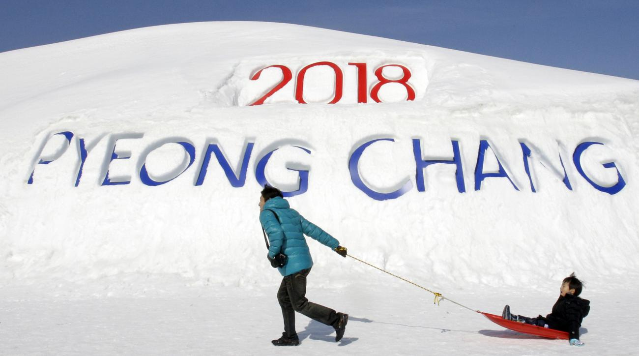 FILE - In this Feb. 19, 2011 file photo, a South Korean father pulls his son on a sled in front of a sign promoting the Pyeongchang 2018 Winter Olympics in Pyeongchang, east of Seoul, South Korea. The people of Pyeongchang can confidently promise two things when they host the Olympics: it'll be cold, and there'll be no concerns about snow. While a warm spell has created challenging conditions for the skiers and snowboarders competing in the mountains above Sochi at the 2014 edition, there's been heavy dumps of snow in the region that will host the next Winter Games in 2018. (AP Photo/ Lee Jin-man, File)