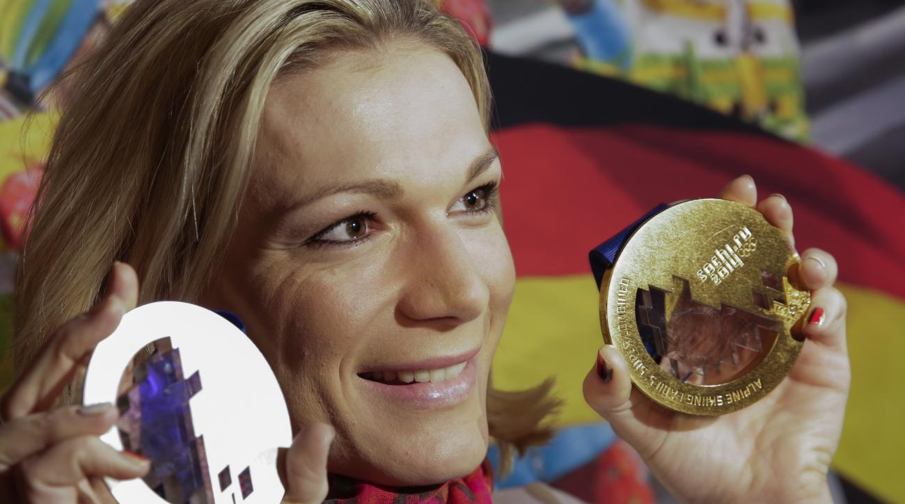 Germany's Maria Hoefl-Riesch poses with her gold and silver medals at the German house at the 2014 Winter Olympics, Saturday, Feb. 15, 2014, in Krasnaya Polyana, Russia. Hoefl-Riesch finished second in the women's super-G after taking the gold medal in the super combined five days earlier. (AP Photo/Gero Breloer)