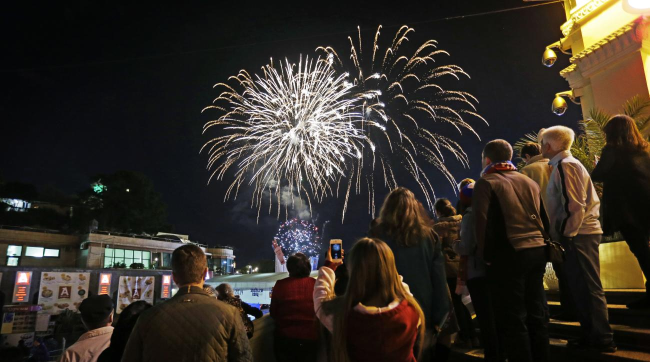 Fireworks go off over the Black Sea as the public gathers at a 2014 Winter Olympics Live Site which broadcasts televised coverage on giant monitors, Saturday, Feb. 15, 2014, in central Sochi, Russia. (AP Photo/David Goldman)