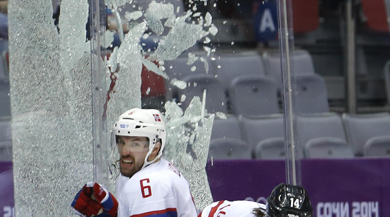 Glass encasing the penalty box shatters as Austria forward Andreas Nodl checks Norway defenseman Jonas Holos in the second period of a men's ice hockey game at the 2014 Winter Olympics, Sunday, Feb. 16, 2014, in Sochi, Russia. (AP Photo/Mark Humphrey)