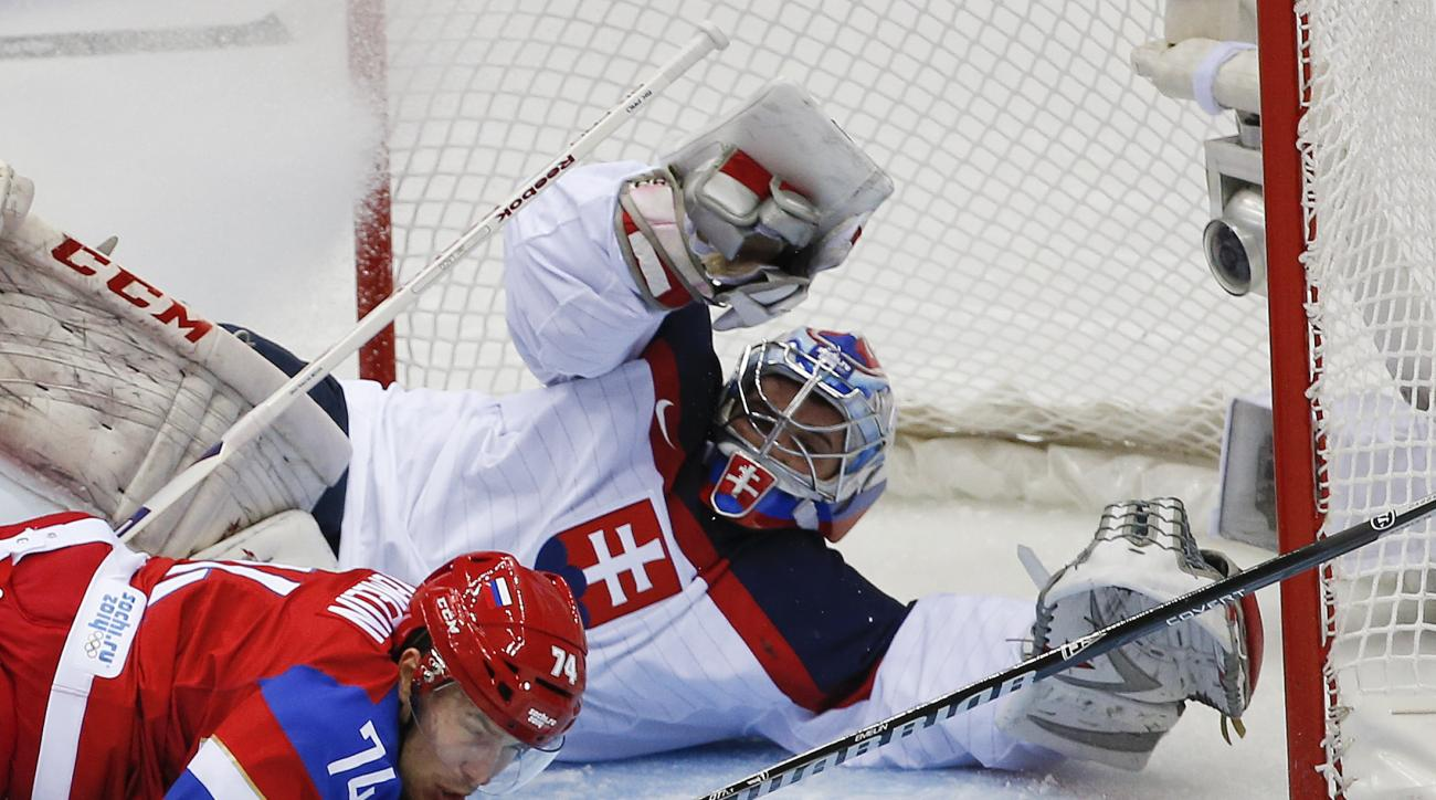 Slovakia goaltender Jan Laco  and Russia defenseman Alexei Yemelin look for the rebound on a shot in the first period of a men's ice hockey game at the 2014 Winter Olympics, Sunday, Feb. 16, 2014, in Sochi, Russia. (AP Photo/Julio Cortez)