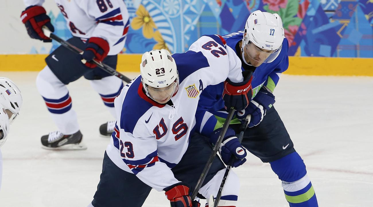 USA forward Dustin Brown takes control of the puck away from Slovenia defenseman Ziga Pavlin during the 2014 Winter Olympics men's ice hockey game at Shayba Arena Sunday, Feb. 16, 2014, in Sochi, Russia. (AP Photo/Petr David Josek)