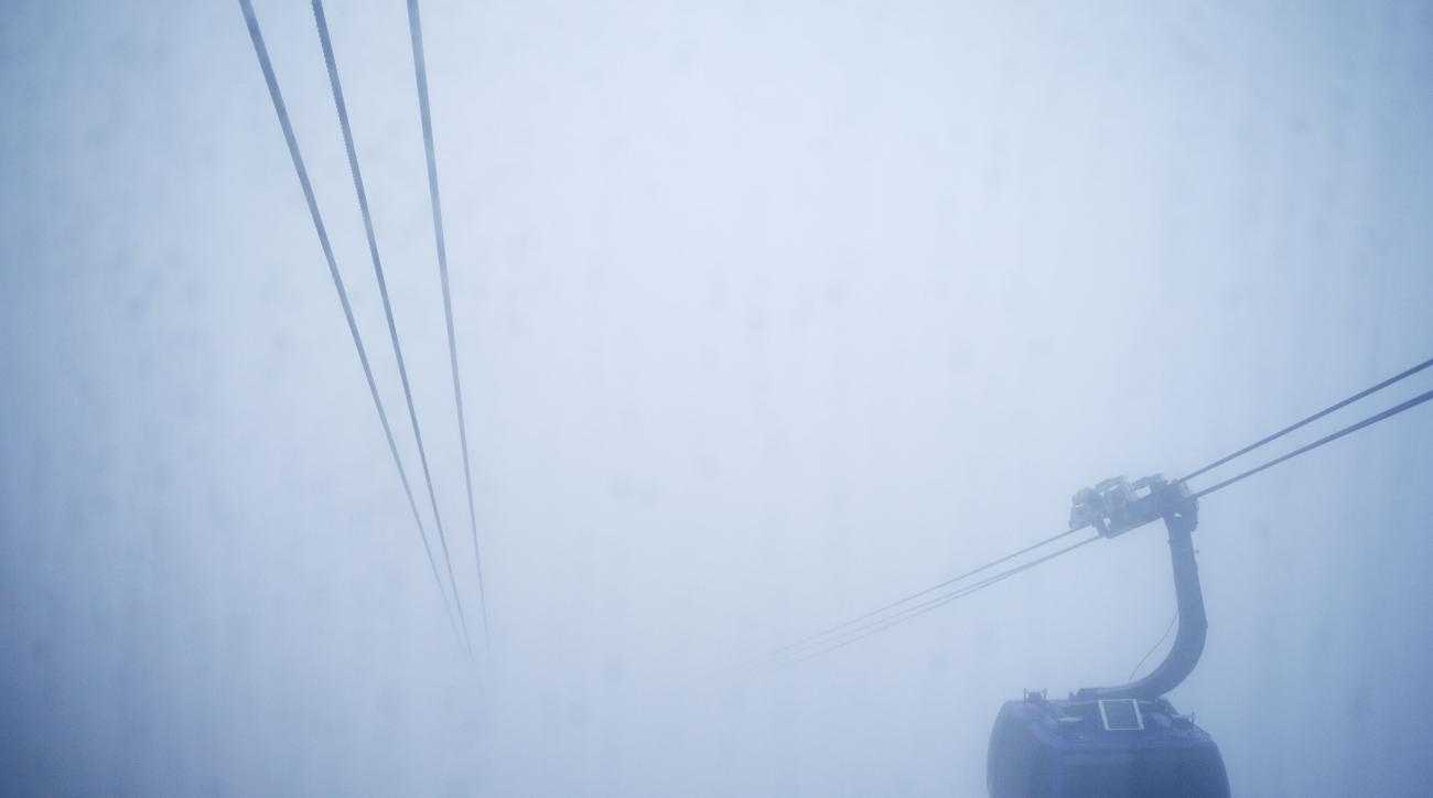 A gondola goes through the fog prior to the men's snowboard cross competition at the Rosa Khutor Extreme Park, at the 2014 Winter Olympics, Monday, Feb. 17, 2014, in Krasnaya Polyana, Russia. (AP Photo/Andy Wong)