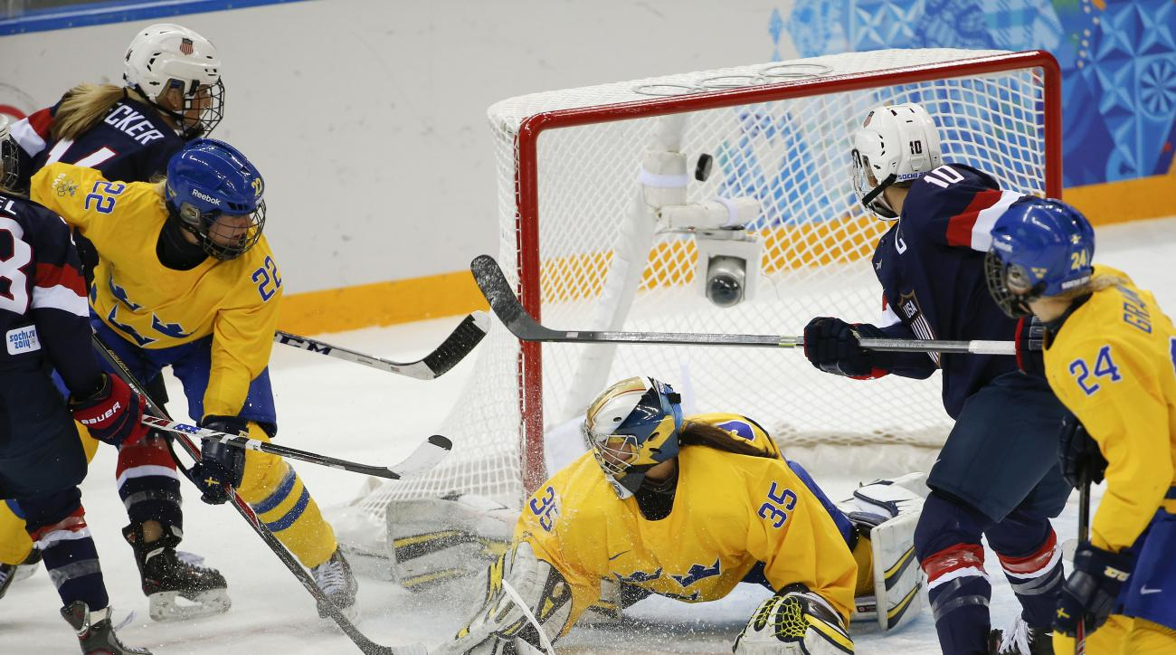 The puck gets past goalkeeper Valentina Wallner of Sweden for a third goal by the USA during the first period of the 2014 Winter Olympics women's semifinal ice hockey game at Shayba Arena Monday, Feb. 17, 2014, in Sochi, Russia. (AP Photo/Julio Cortez)