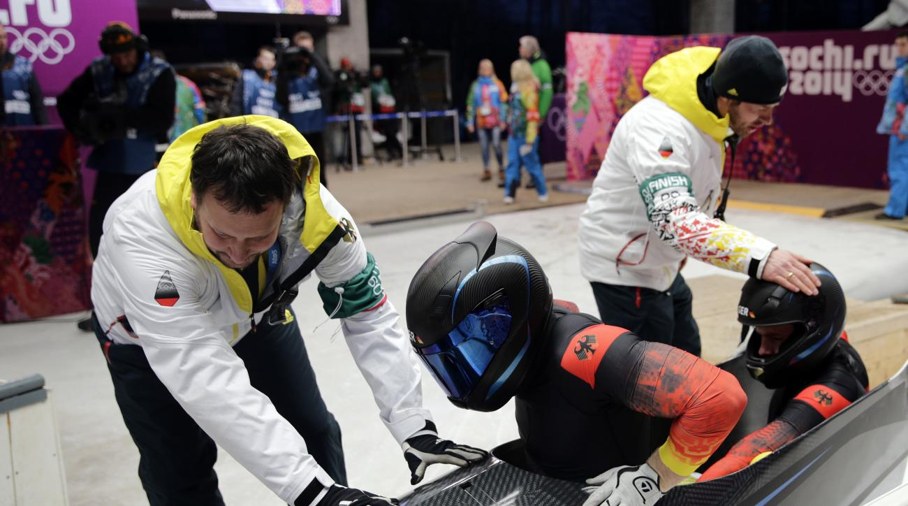 The team from Germany GER-1, piloted by Francesco Friedrich and brakeman Jannis Baecker, get help out of their sled after the third run during the men's two-man bobsled competition at the 2014 Winter Olympics, Monday, Feb. 17, 2014, in Krasnaya Polyana, Russia. (AP Photo/Jae C. Hong)