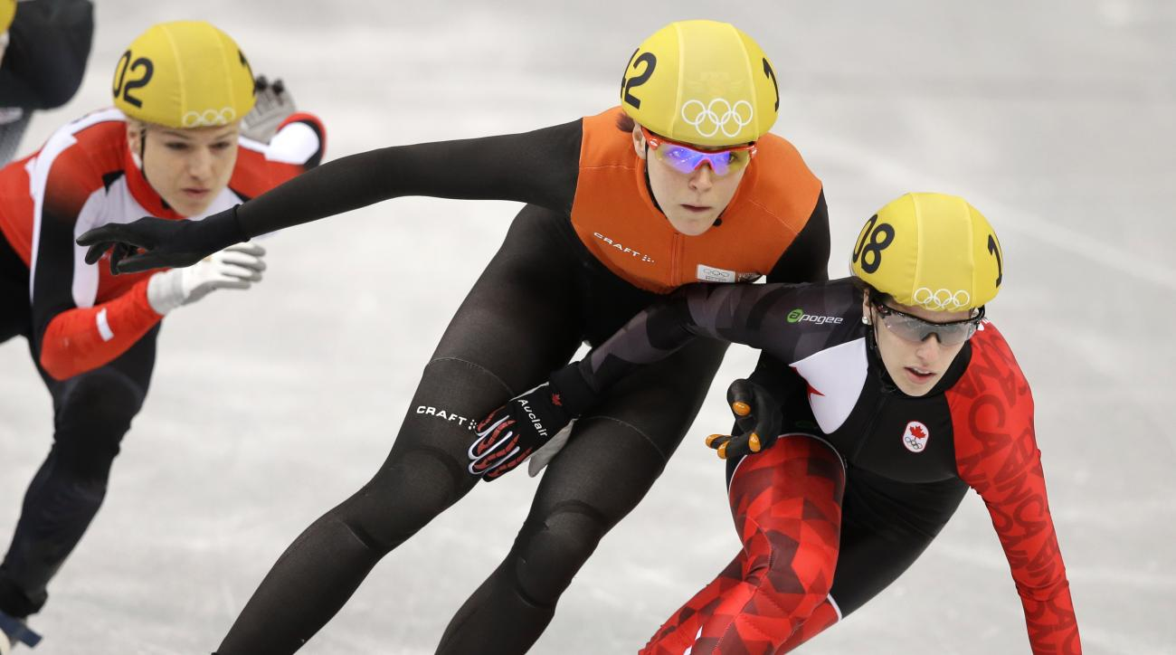 Marianne St-Gelais of Canada, right, and Jorien ter Mors of the Netherlands, centre, compete in a women's 1000m short track speedskating heat at the Iceberg Skating Palace during the 2014 Winter Olympics, Tuesday, Feb. 18, 2014, in Sochi, Russia. (AP Photo/Darron Cummings)