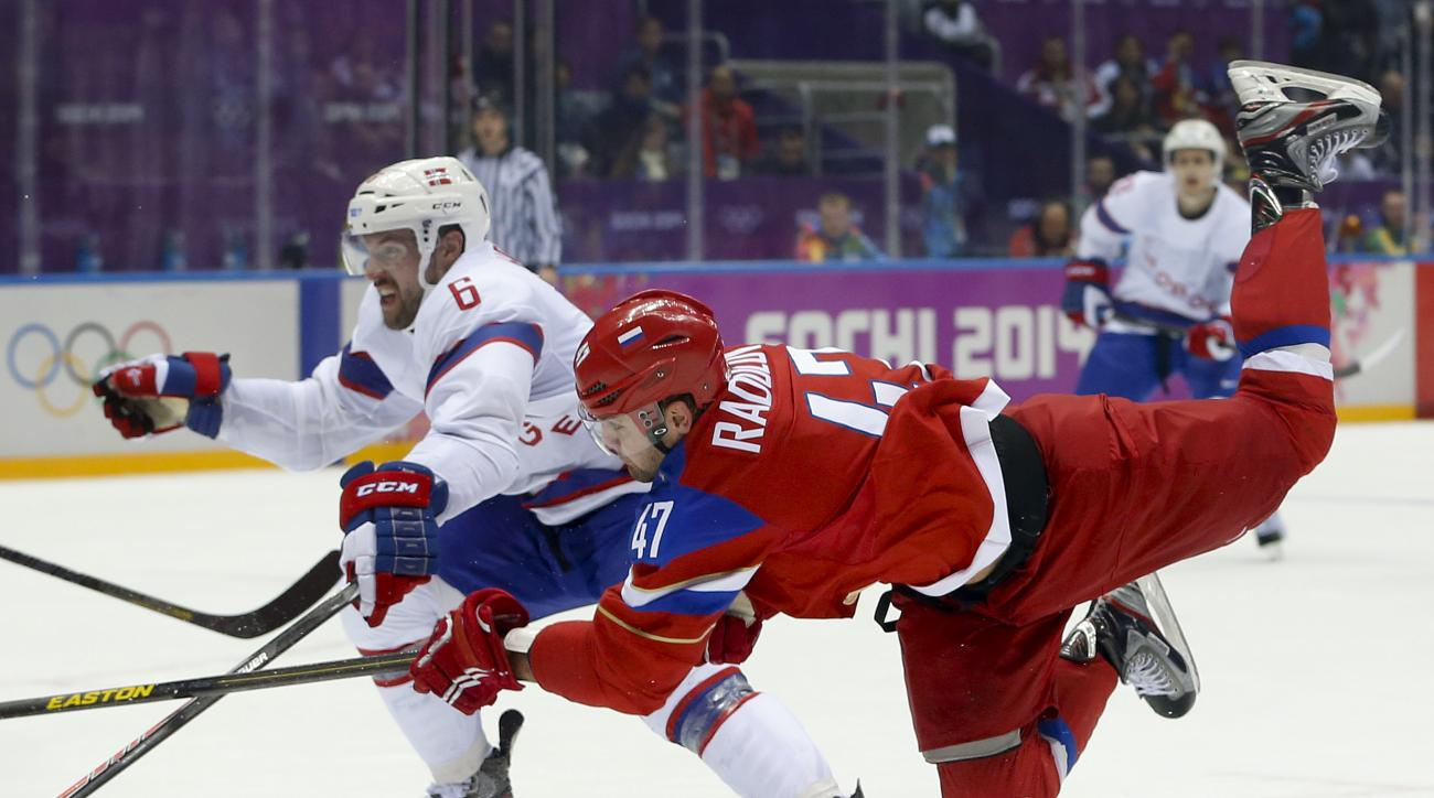 Russia forward Alexander Radulov makes an off-balance shot against Norway defenseman Jonas Holos in the second period of a men's ice hockey game at the 2014 Winter Olympics, Tuesday, Feb. 18, 2014, in Sochi, Russia. (AP Photo/Mark Humphrey)