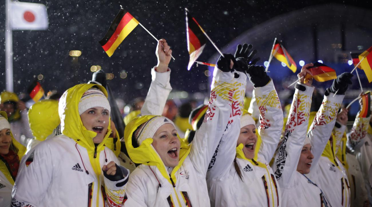 Fans, waving German flags, cheer for the ski jumping team gold medalists from Germany during their medals ceremony at the 2014 Winter Olympics, Tuesday, Feb. 18, 2014, in Sochi, Russia. (AP Photo/David Goldman)