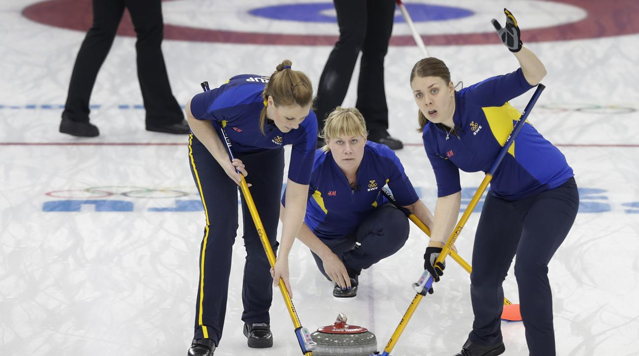 Sweden's Maria Prytz, center, delivers the rock while her teammates Christina Bertrup, left, and Maria Wennerstroem, right, sweeps the ice sheet during the women's curling semifinal game against  at the 2014 Winter Olympics, Wednesday, Feb. 19, 2014, in Sochi, Russia. (AP Photo/Wong Maye-E)