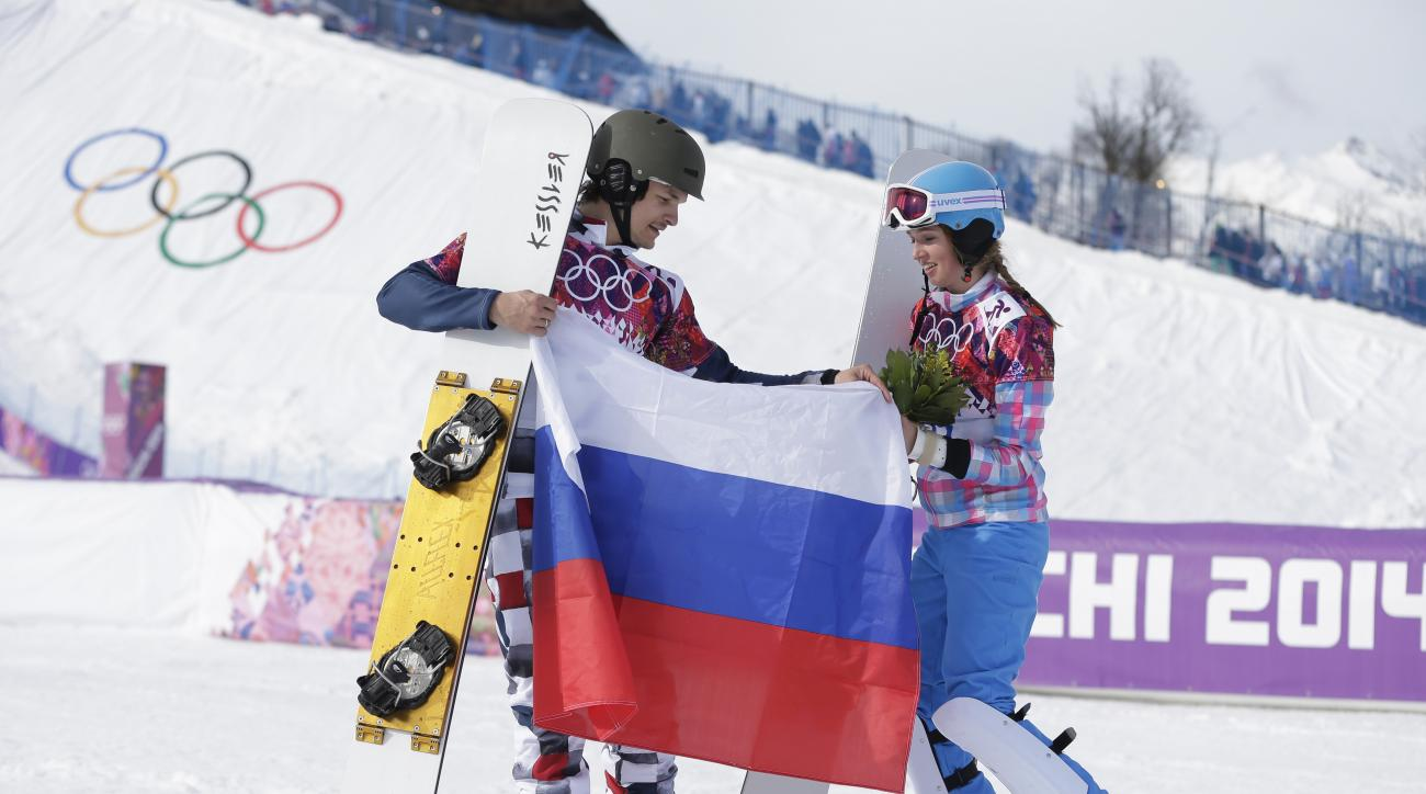 Men's snowboard parallel giant slalom gold medalist Vic Wild of Russia, left, celebrates with his wife and bronze medalist in the women's snowboard parallel giant slalom final, Russia's Alena Zavarzina, at the Rosa Khutor Extreme Park, at the 2014 Winter Olympics, Wednesday, Feb. 19, 2014, in Krasnaya Polyana, Russia.  (AP Photo/Andy Wong)