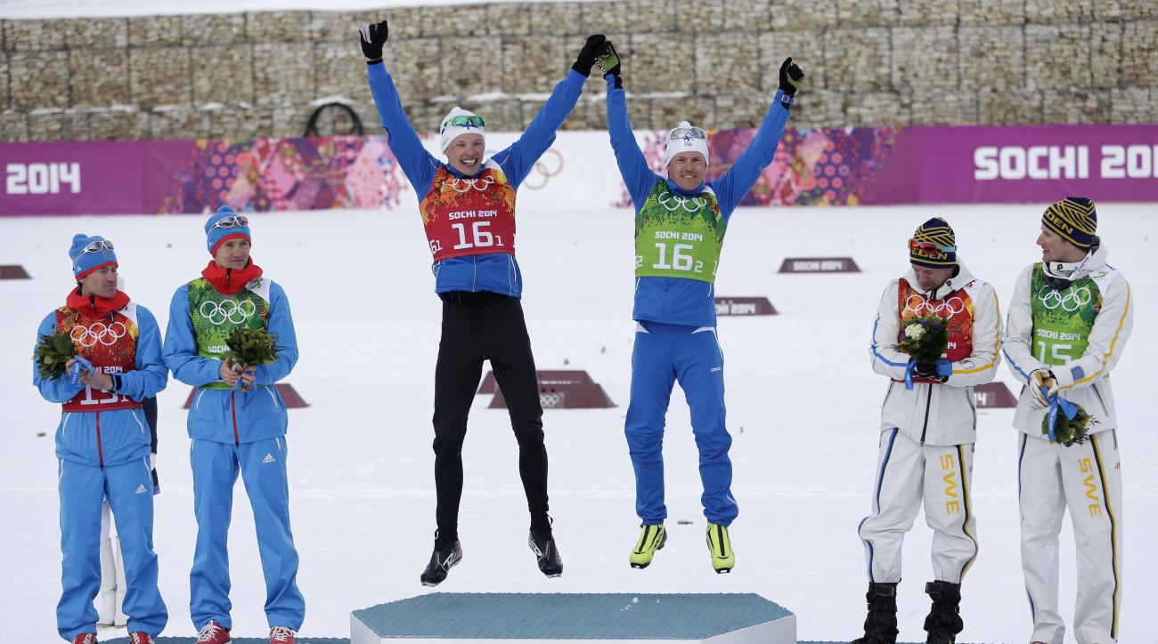 Finland's gold medal winners Iivo Niskanen and Sami Jauhojaervi are flanked by Russia's  silver medal winners Maxim Vylegzhanin, left, and Nikita Kriukov and Sweden's bronze medal winner Emil Joensson and Teodor Peterson, right, during the flower ceremony of the men's classical-style cross-country team sprint competitions at the 2014 Winter Olympics, Wednesday, Feb. 19, 2014, in Krasnaya Polyana, Russia. (AP Photo/Matthias Schrader)