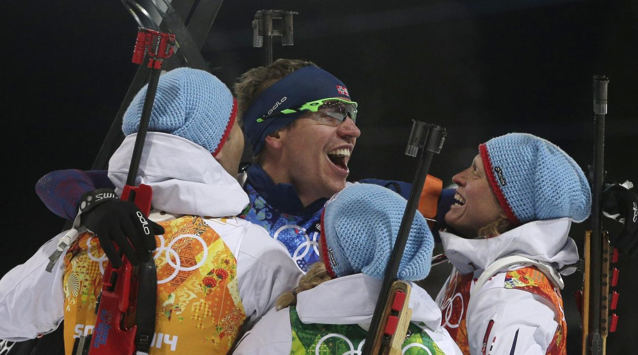 Norway's relay team Tora Berger, Tiril Eckhoff and Ole Einar Bjoerndalen, from right, congratulate Emil Hegle Svendsen, center, after winning the gold during the mixed biathlon relay, at the 2014 Winter Olympics, Wednesday, Feb. 19, 2014, in Krasnaya Polyana, Russia. (AP Photo/Matthias Schrader)